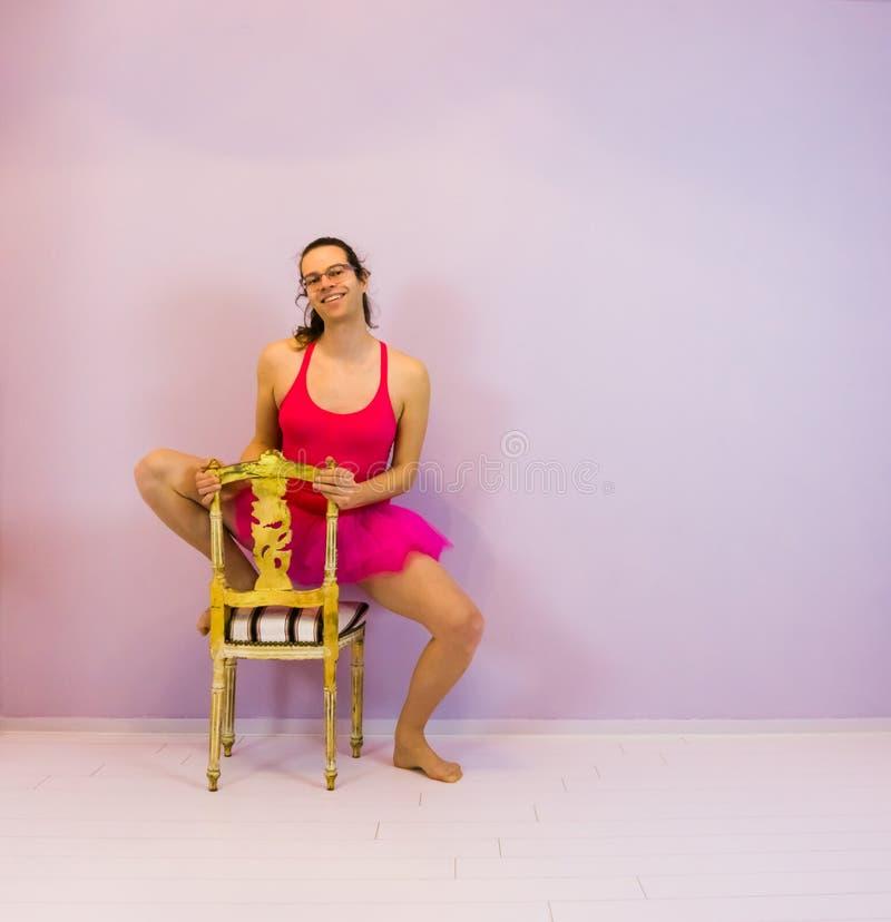 Muchacha de baile joven del ballet del transexual que presenta en una silla, retrato de LGBT en el deporte imagen de archivo
