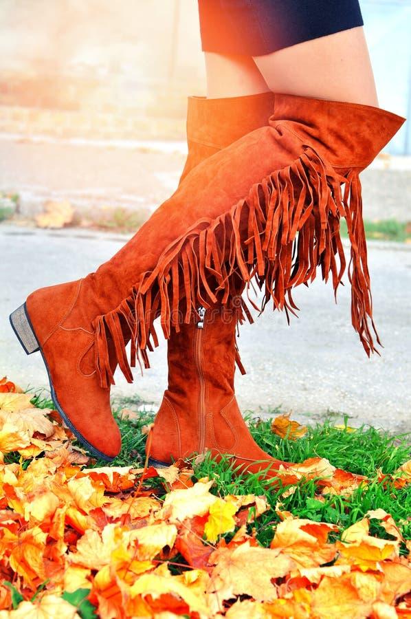 Muchacha de Boho que camina en botas hasta las rodillas de la franja en el día del otoño fotos de archivo