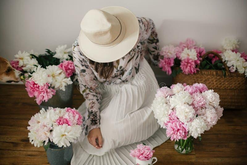 Muchacha de Boho que se sienta con su perro en las peonías del rosa y blancas en piso de madera rústico Mujer elegante del inconf foto de archivo libre de regalías