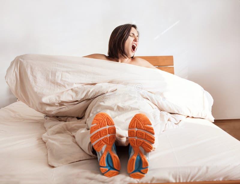 Muchacha de bostezo Wake up en los zapatos funcionados con que se sientan en cama foto de archivo libre de regalías