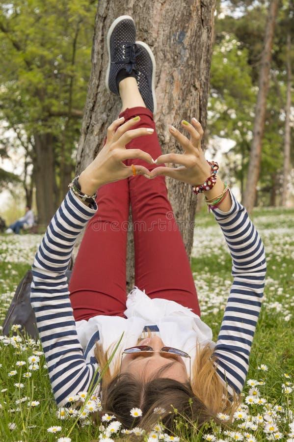 Muchacha de Bunette que miente en la hierba con sus piernas que descansan sobre un árbol fotos de archivo
