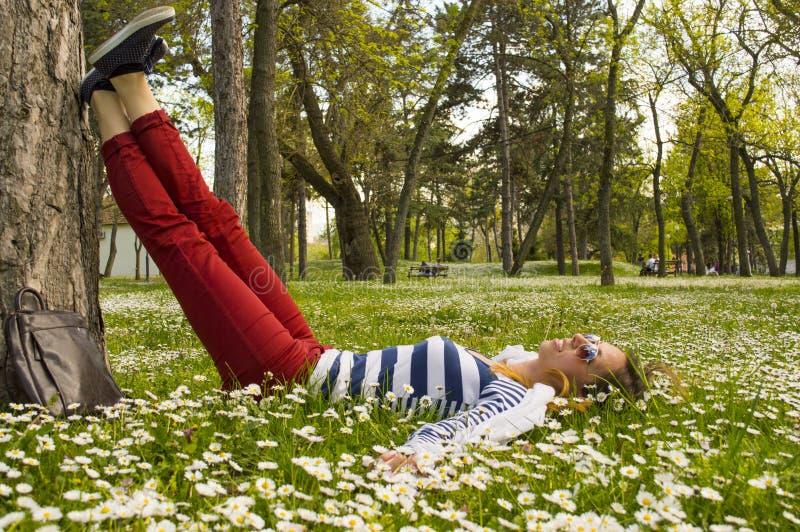 Muchacha de Bunette que miente en la hierba con sus piernas que descansan sobre un árbol fotografía de archivo libre de regalías