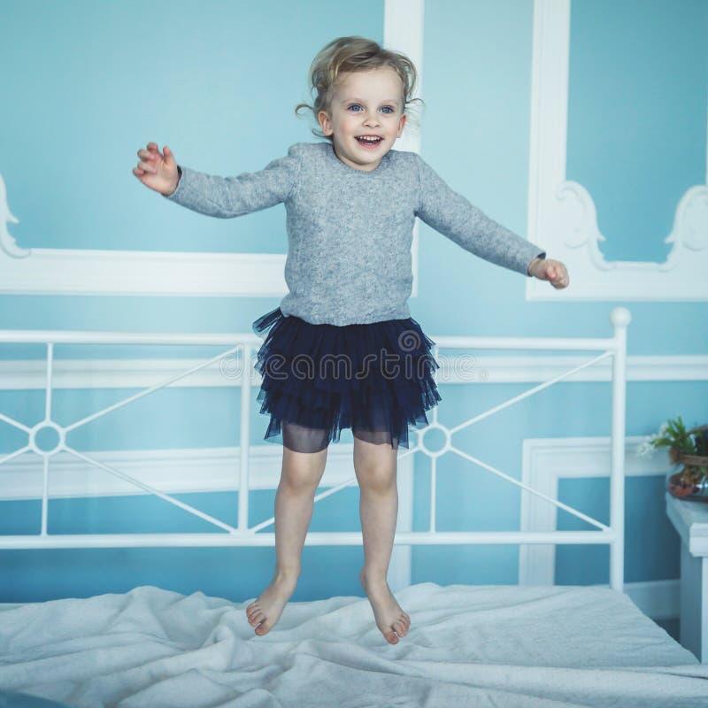 Muchacha de cinco años feliz que salta en la cama imagen de archivo libre de regalías