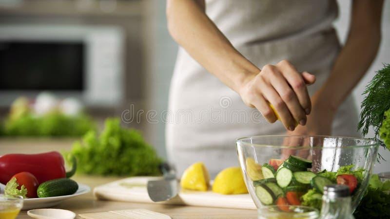 Muchacha de cocinar joven que exprime el jugo de limón fresco en el cuenco de ensalada, vegano, verduras imagen de archivo