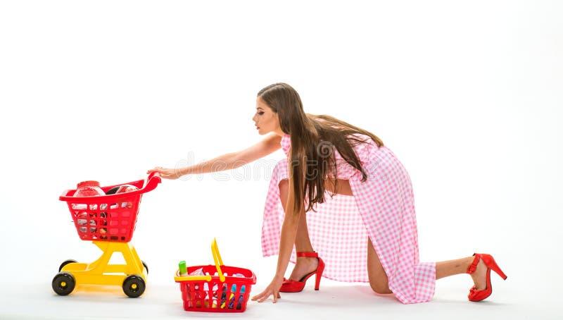 muchacha de compras con el carro lleno Servicio a domicilio la mujer retra va a hacer compras mujer del ama de casa del vintage a imágenes de archivo libres de regalías