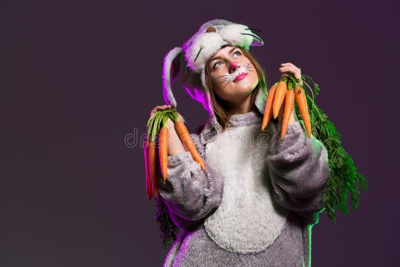 Muchacha de conejito pensativa de pascua al manojo de zanahorias imagen de archivo libre de regalías