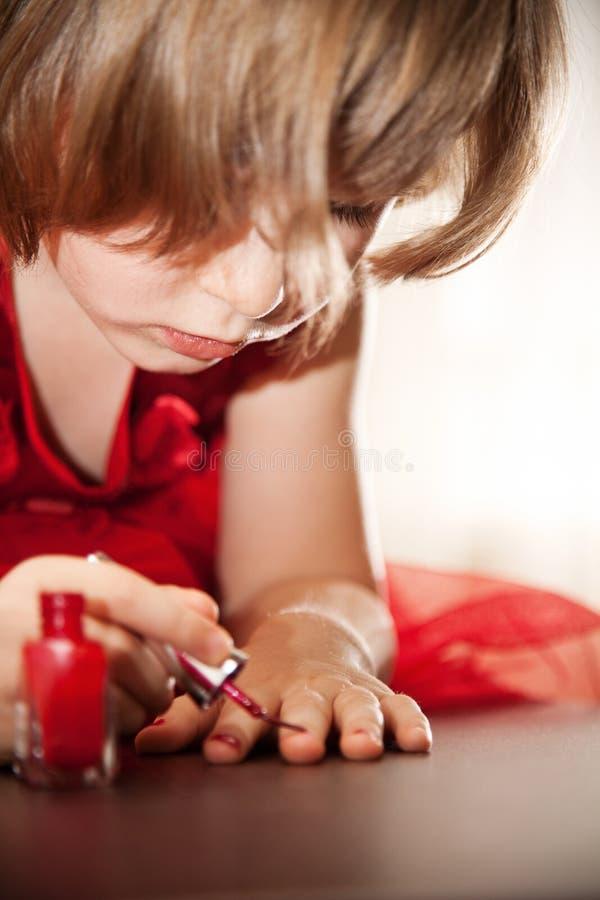 Niña en rojo clavos pintados un vestido con el esmalte de uñas foto de archivo libre de regalías