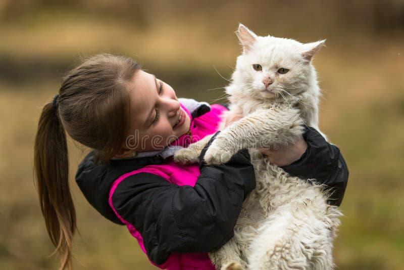 Muchacha de diez años que juega con un gato perdido Amor imágenes de archivo libres de regalías