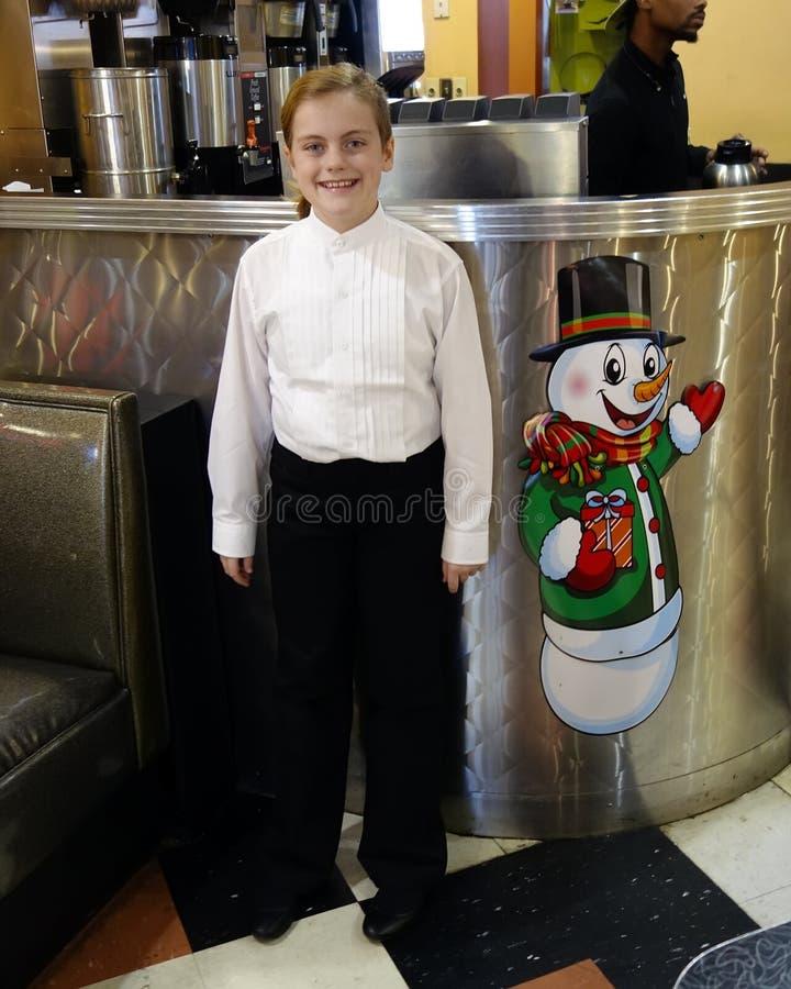 Muchacha de diez años sonriente que se coloca al lado de una imagen de un muñeco de nieve fotografía de archivo