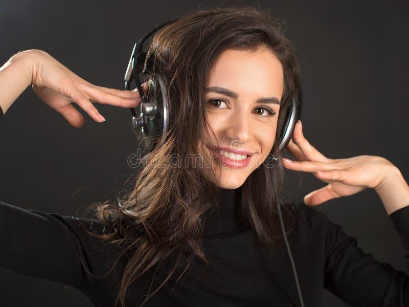 Muchacha de DJ en los golpes del disco de los auriculares que escuchan que presentan en estudio sobre fondo oscuro Modelo caucási fotografía de archivo