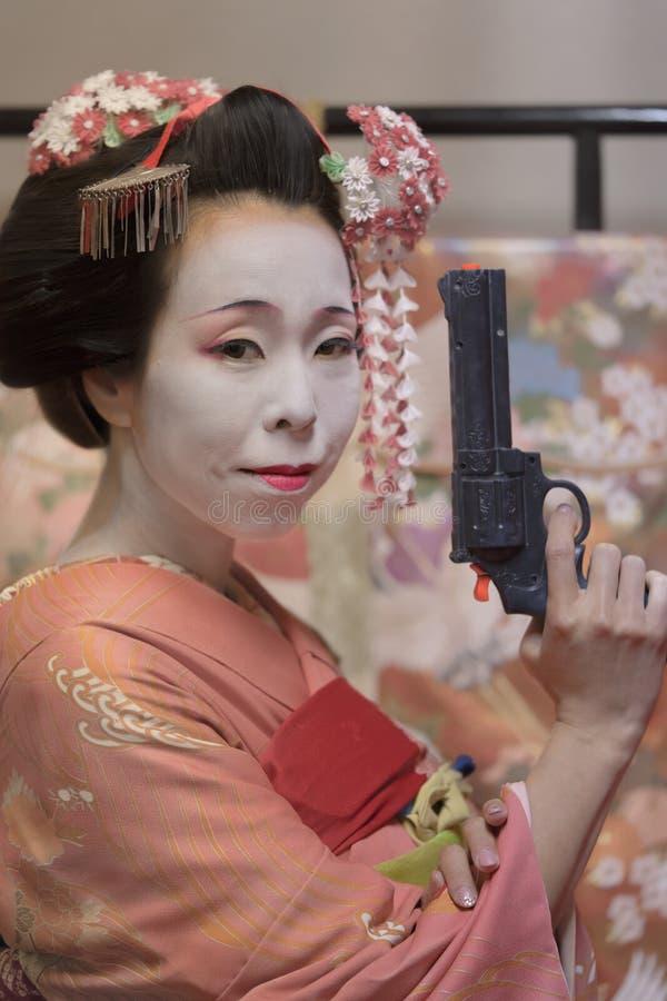 Muchacha de geisha en el kimono que sostiene un arma plástico en su mano fotografía de archivo