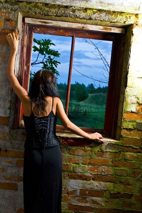 Muchacha de Goth en la ventana fotos de archivo libres de regalías