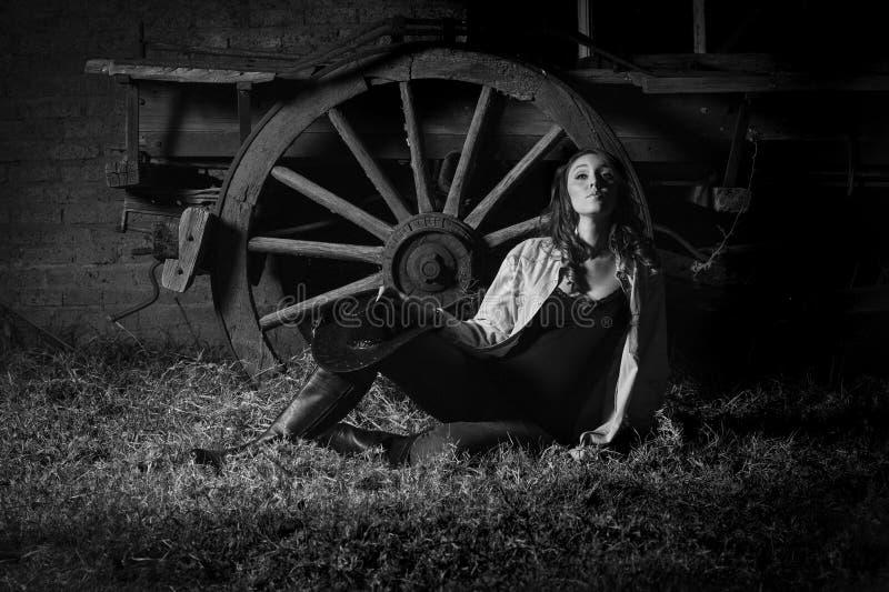 Muchacha de granja hermosa que se inclina contra el carro viejo imágenes de archivo libres de regalías