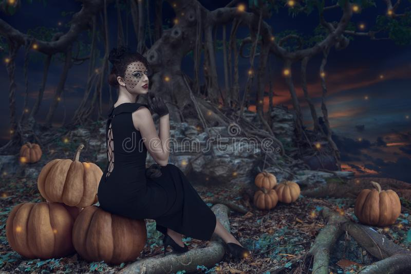 Muchacha de Halloween en bosque oscuro imagenes de archivo