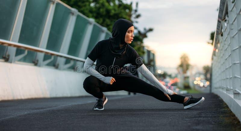 Muchacha de Hijab que ejercita al aire libre en madrugada imágenes de archivo libres de regalías