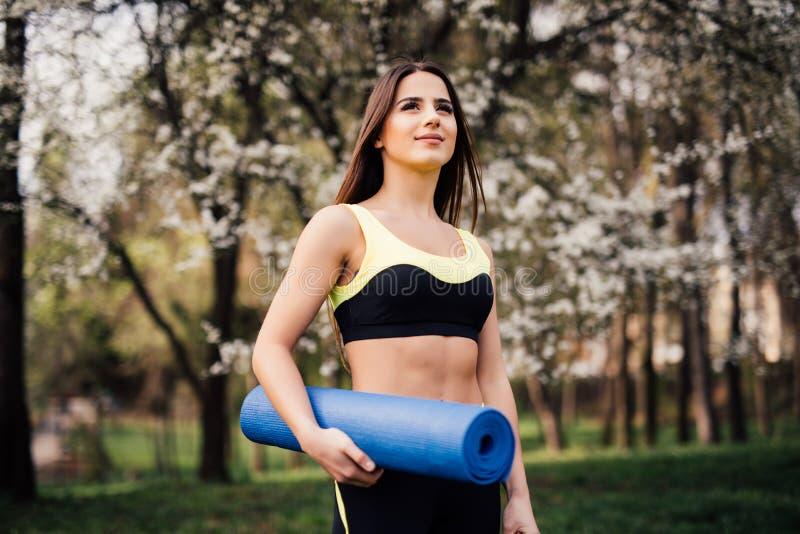 Muchacha de la aptitud con la estera de la yoga que se coloca al aire libre en la naturaleza - mujer apta con el accesorio del ej imágenes de archivo libres de regalías