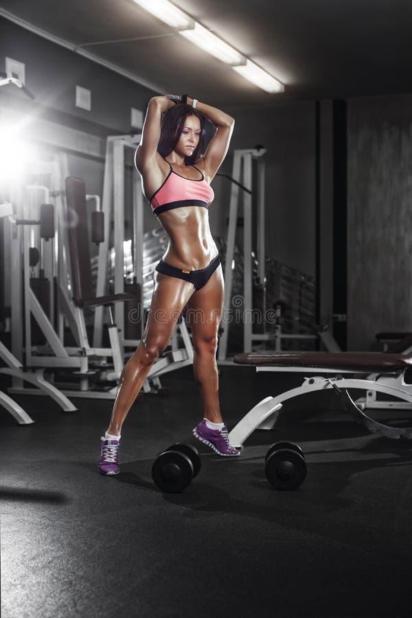 Muchacha de la aptitud con las pesas de gimnasia que presentan en el gimnasio foto de archivo libre de regalías