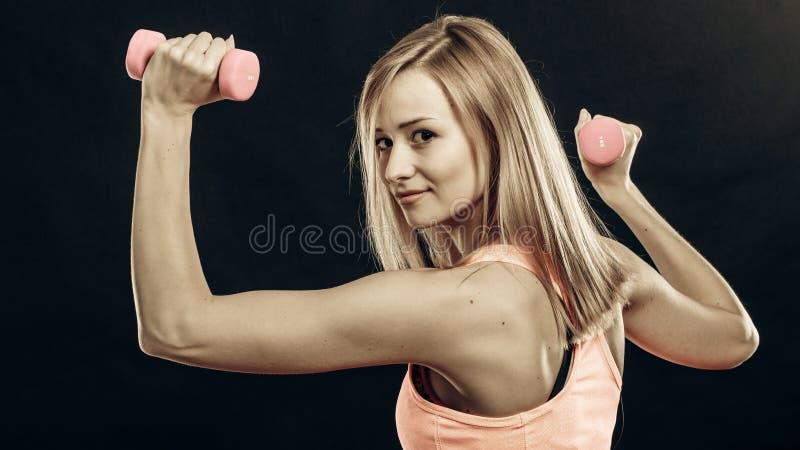 Muchacha de la aptitud con las pesas de gimnasia que doblan los m?sculos en gimnasio imagen de archivo libre de regalías