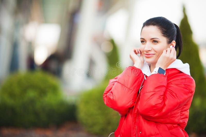 Muchacha de la aptitud M?sica de funcionamiento y que escucha de la muchacha deportiva bonita al aire libre Forma de vida sana en imagen de archivo libre de regalías