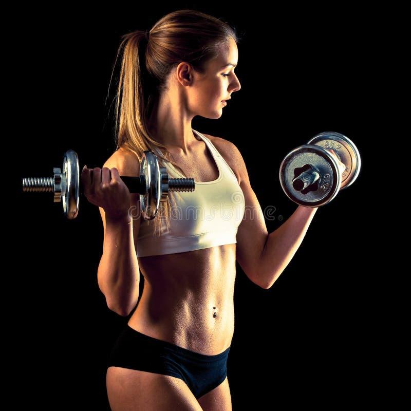 Muchacha de la aptitud - mujer joven atractiva que se resuelve con pesas de gimnasia imagenes de archivo