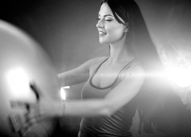 Muchacha de la aptitud que ejercita en gimnasio con el fitball foto de archivo