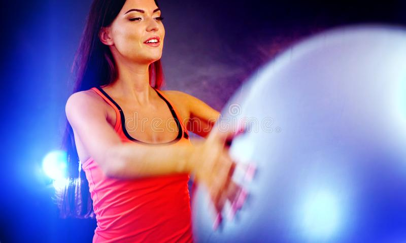 Muchacha de la aptitud que ejercita en gimnasio con el fitball fotografía de archivo