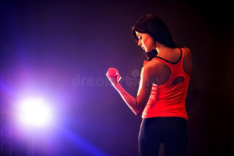 Muchacha de la aptitud que ejercita en gimnasio con pesas de gimnasia foto de archivo