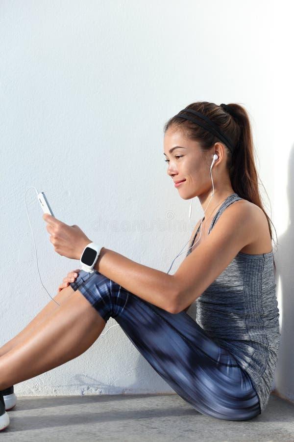 Muchacha de la aptitud que elige la música de la motivación que escucha para llamar por teléfono al app y a llevar imagen de archivo libre de regalías