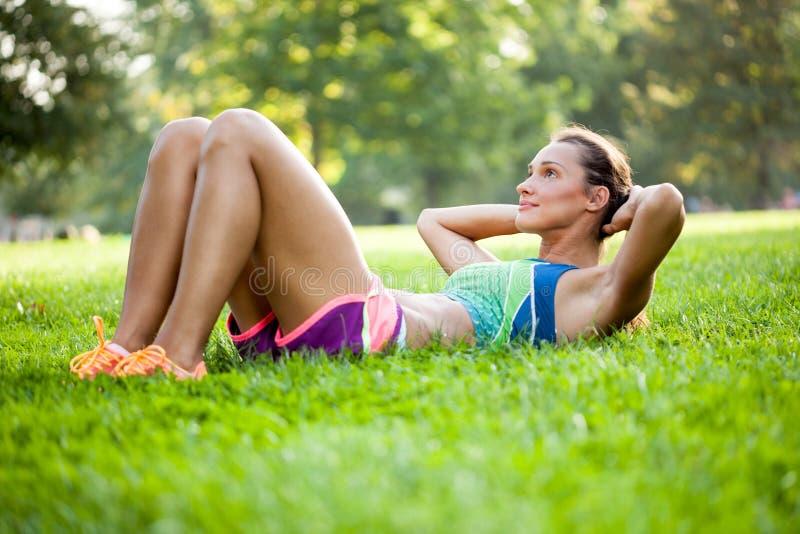 Muchacha de la aptitud que hace sentar-UPS en un parque en la hierba fotografía de archivo