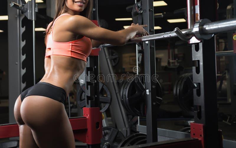 Muchacha de la aptitud que presenta en el gimnasio imagen de archivo