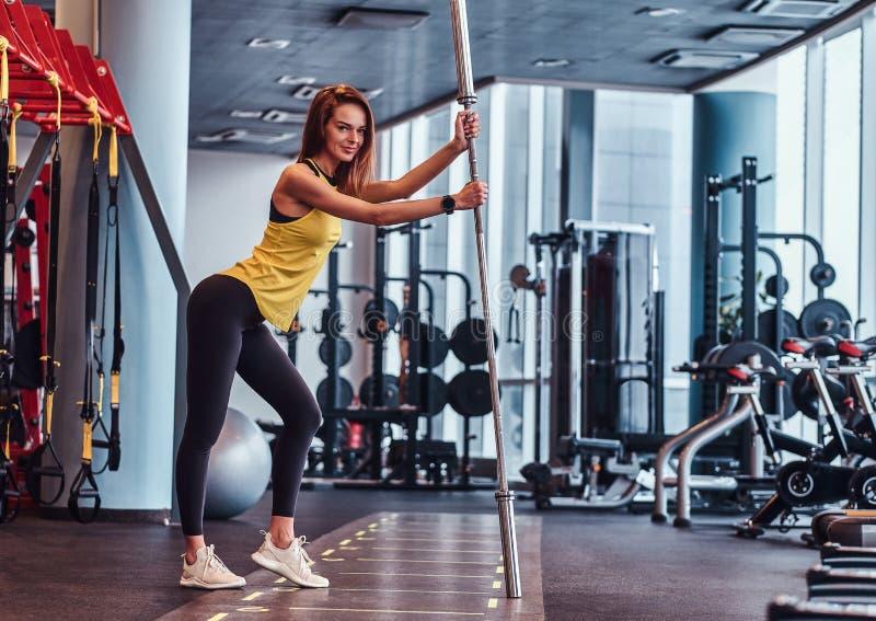 Muchacha de la aptitud que presenta para una cámara mientras que se inclina en un barbell en el gimnasio moderno foto de archivo libre de regalías