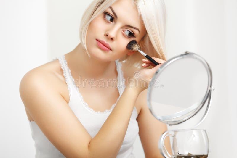 Muchacha de la belleza con el cepillo del maquillaje. El diario compensa a la mujer rubia. Sea imagenes de archivo