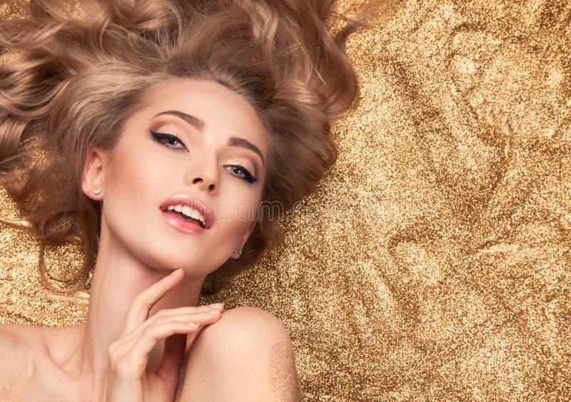 Muchacha de la belleza de la moda que miente en brillo de oro fotos de archivo libres de regalías