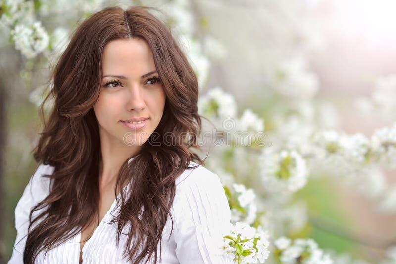 Muchacha de la belleza de primavera La mujer joven hermosa en un parque del verano aventaja imagen de archivo libre de regalías