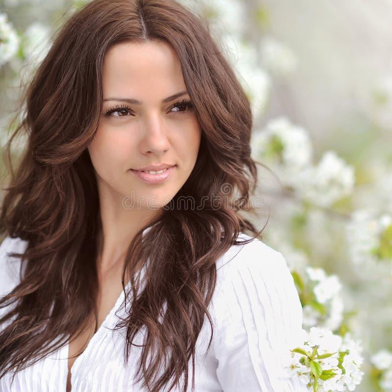 Muchacha de la belleza de primavera La mujer joven hermosa en un parque del verano aventaja fotografía de archivo libre de regalías