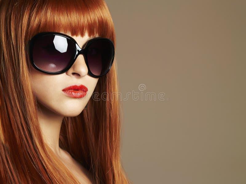 Muchacha de la belleza en gafas de sol Pelo rojo sano Mujer joven hermosa con los labios rojos imagen de archivo