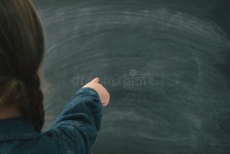 Muchacha de la educación escolar que señala la pizarra en blanco foto de archivo