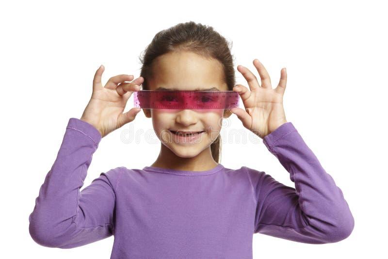 Muchacha de la escuela con la regla rosada foto de archivo libre de regalías