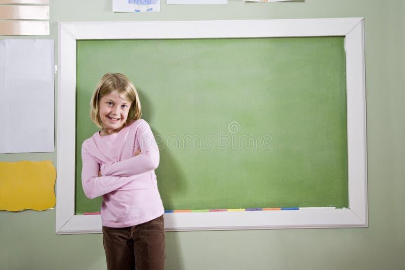 Muchacha de la escuela en pizarra que hace una pausa de la sala de clase fotografía de archivo libre de regalías