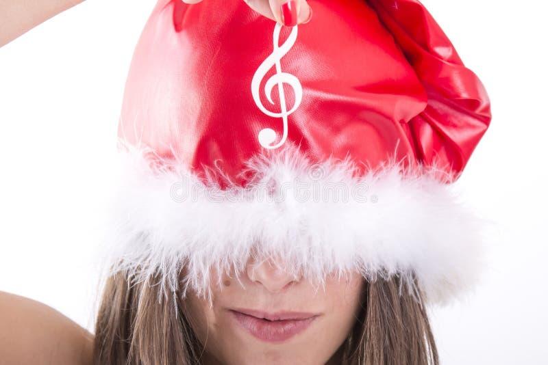 Muchacha de la feliz Navidad que muestra la nota musical blanca foto de archivo libre de regalías