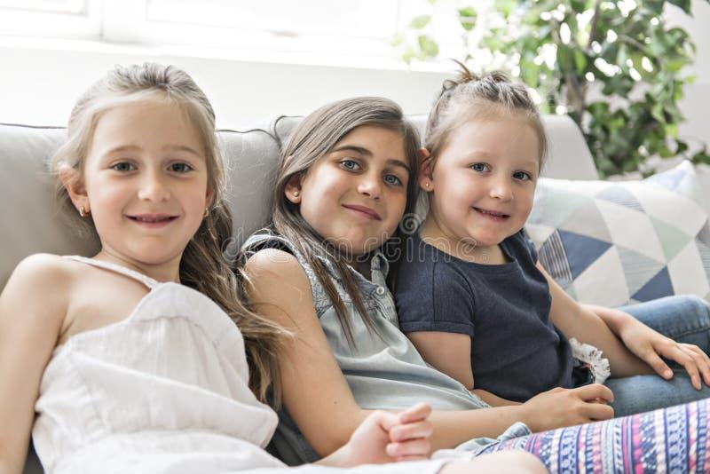 Muchacha de la hermana de los mejores amigos en el sofá que se divierte fotos de archivo libres de regalías