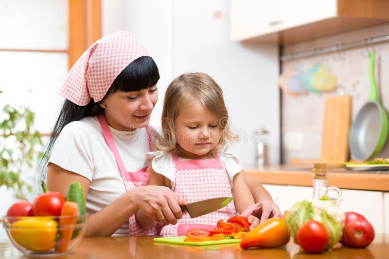 Muchacha de la madre y del niño que cocina y que corta verduras en cocina fotografía de archivo