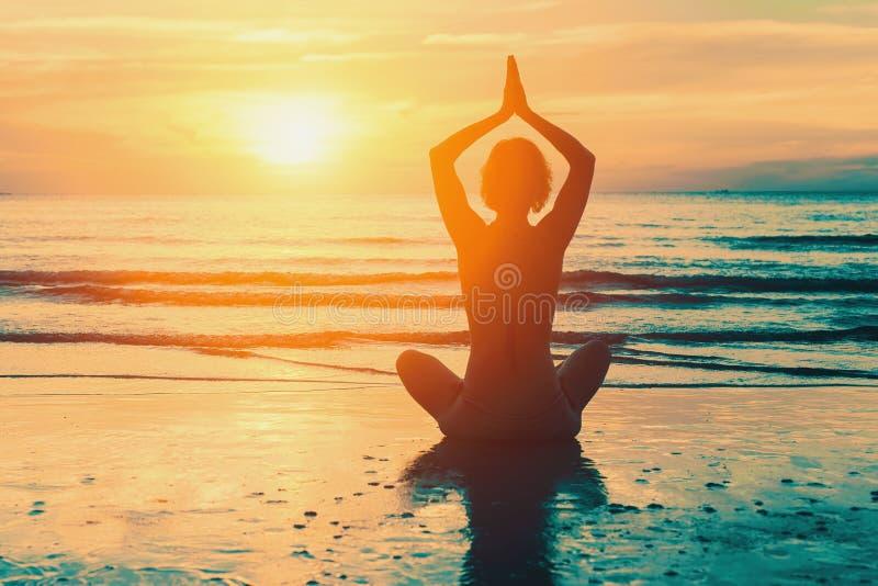Muchacha de la meditación en el mar durante puesta del sol imagen de archivo libre de regalías