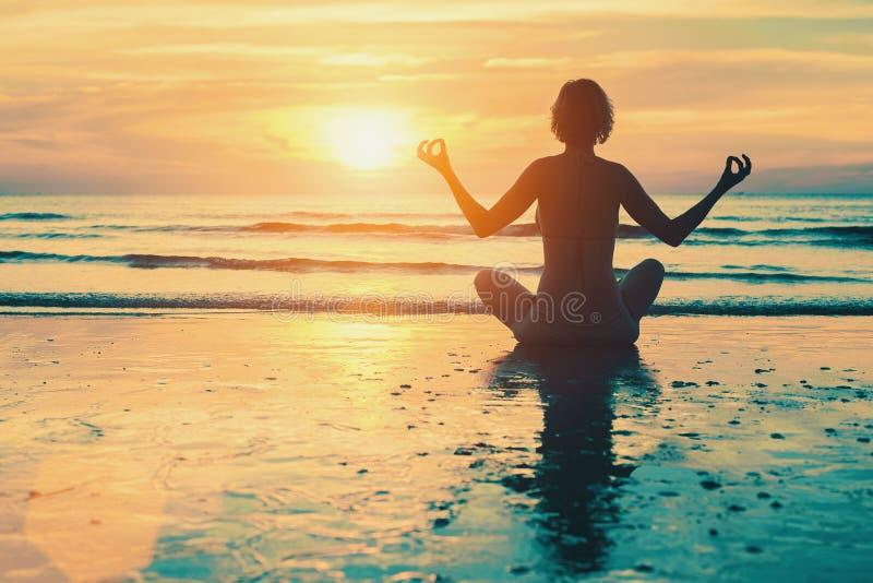 Muchacha de la meditación en el mar durante puesta del sol fotos de archivo