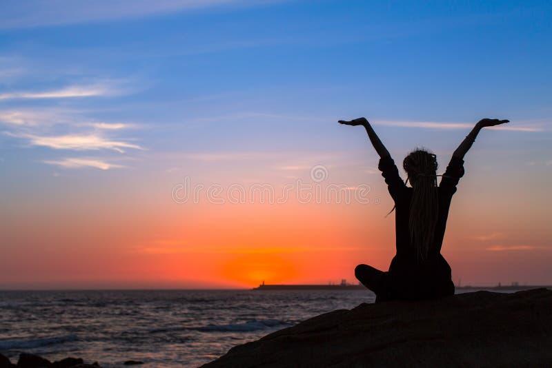 Muchacha de la meditación en el mar durante puesta del sol foto de archivo libre de regalías
