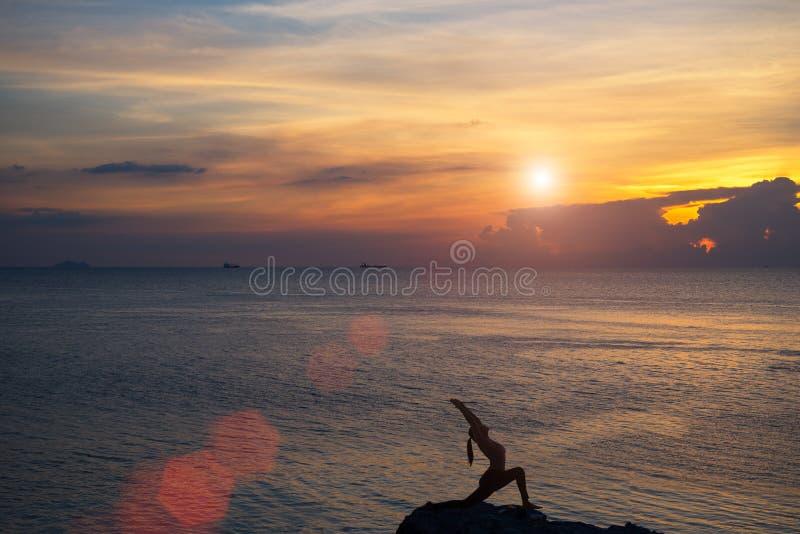 Muchacha de la meditación en el mar durante puesta del sol Silueta de la yoga fotos de archivo