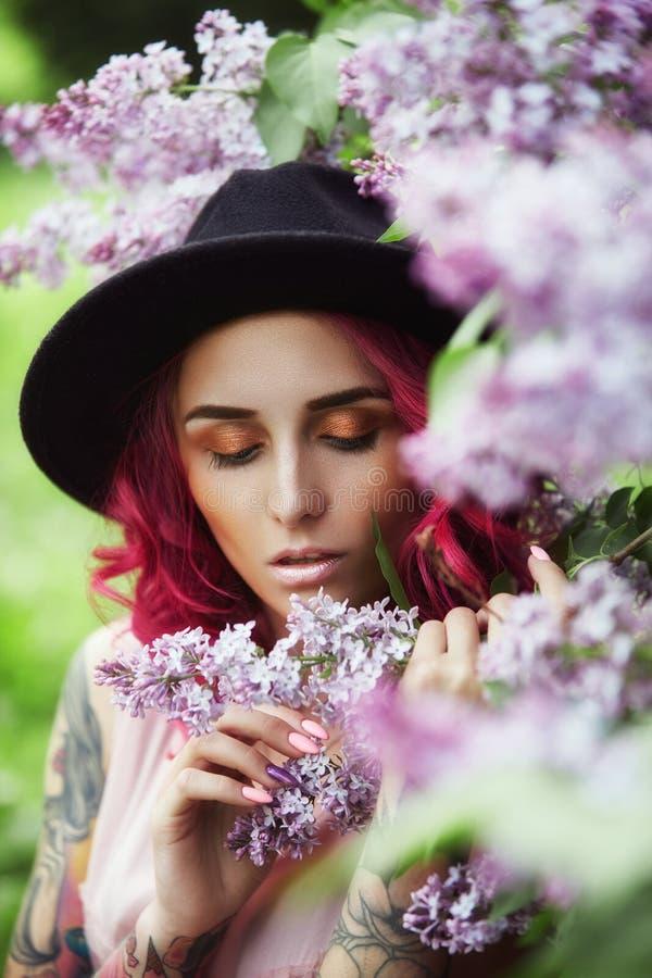 Muchacha de la moda con el pelo rojo y el sombrero redondo grande, retrato de la primavera en colores de la lila en verano Vestid foto de archivo libre de regalías
