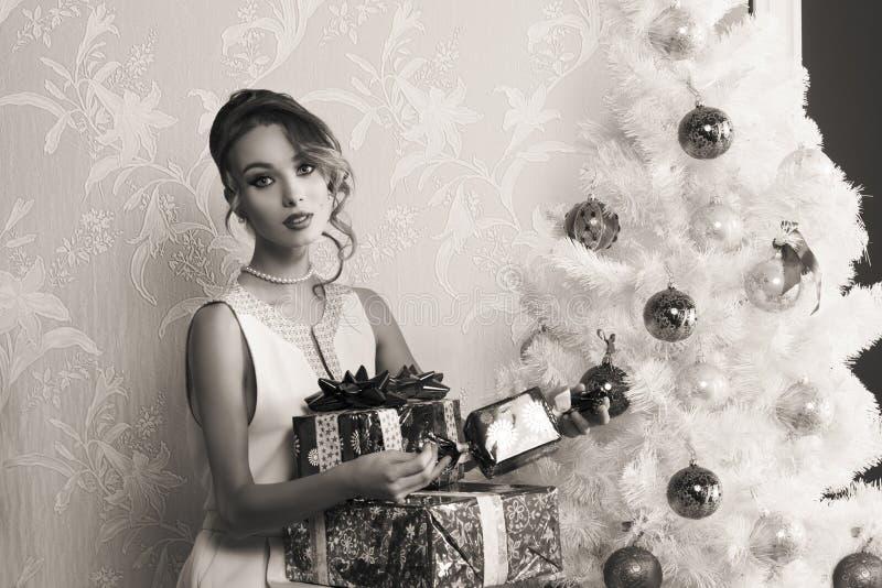 Muchacha de la moda con los regalos de Navidad en BW fotografía de archivo libre de regalías
