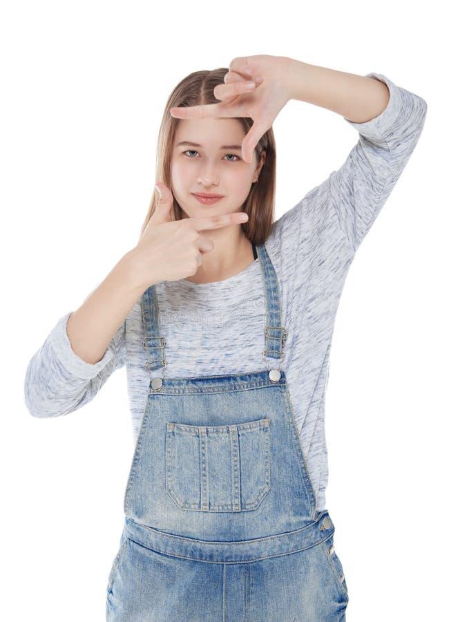 Muchacha de la moda de los jóvenes que mira a través del marco de las manos aislado imagen de archivo