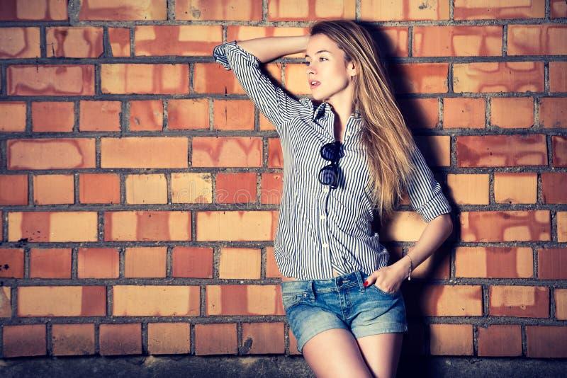 Muchacha de la moda del estilo de la calle en la pared de ladrillo imágenes de archivo libres de regalías